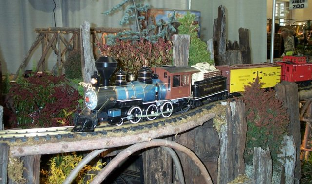 Trains in a miniature train garden landscape with real plants