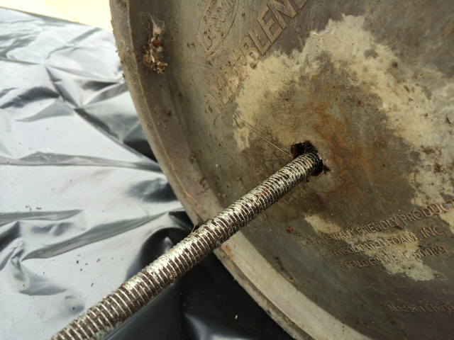 Inserting a metal rod in a clogged drainage hole