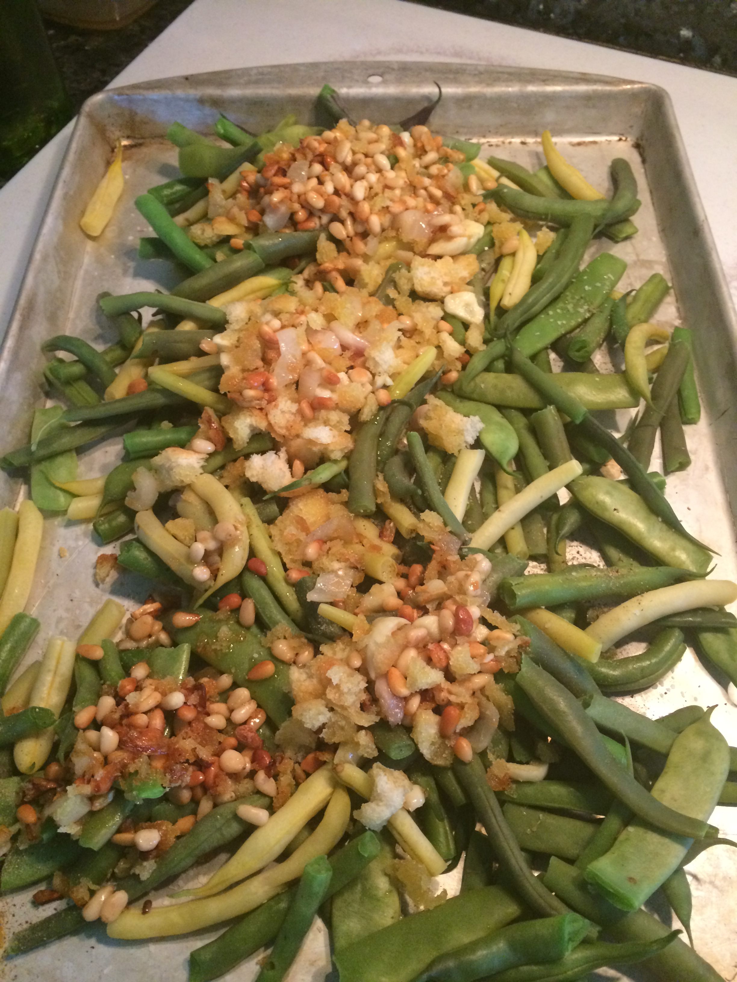 Loading the cookie sheet with green beans, garlic, olive oil, pine ...