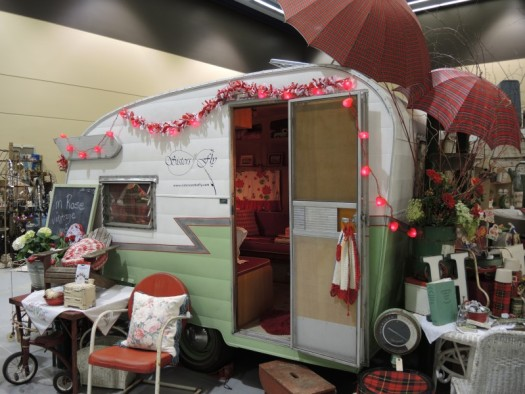 An old trailer that displays vintage gardening equipment at the Northwest Flower and Gardening Show