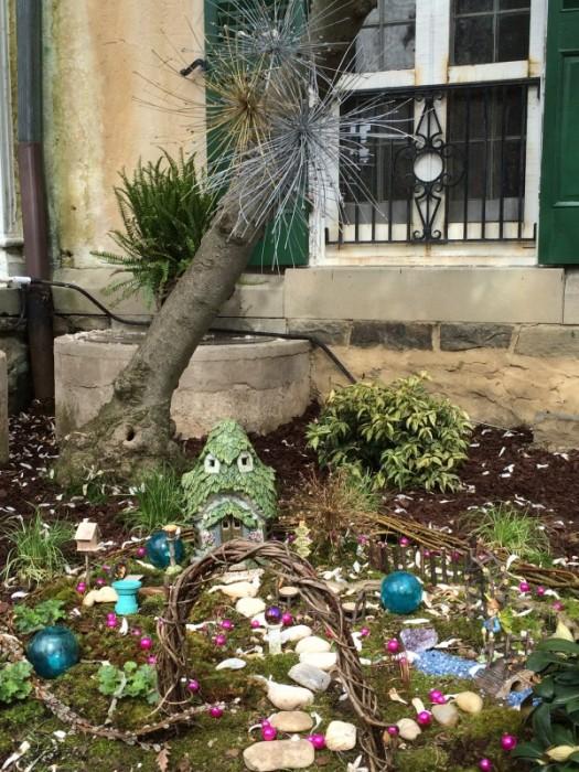 Seedheads of allium suspended over fairy garden